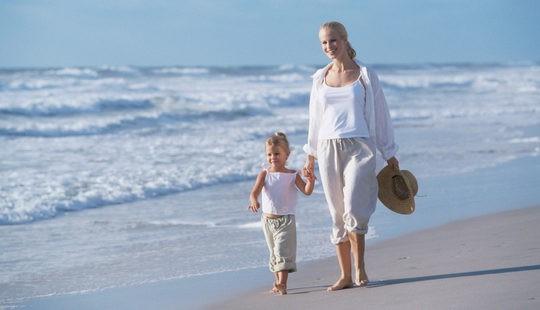 Madre soltera paseando con su hijo por la playa