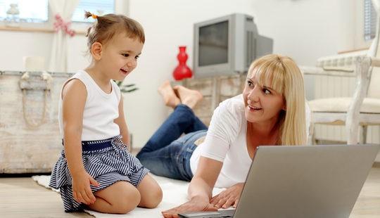Madre jugando con su hijo en el ordenador