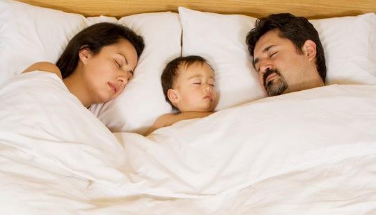 Bebé durmiendo en la cama de sus padres