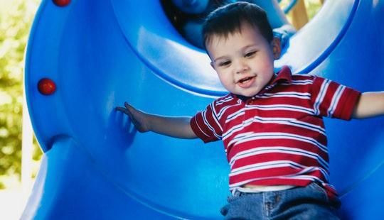Niño tirándose por un tobogán del parque