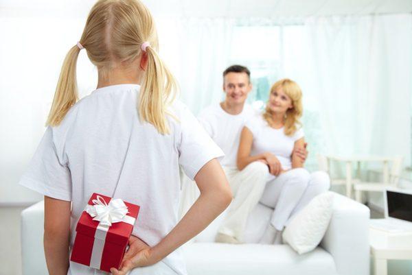 Niña antes de darle el regalo a su padre