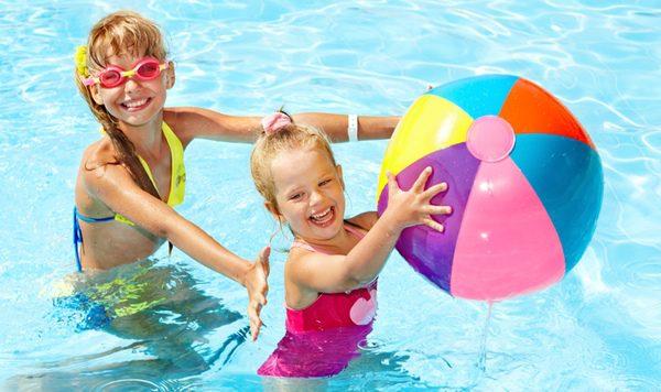 Dos niñas jugando en la piscina en verano