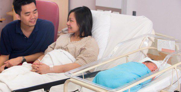 Pareja junto a su hijo recién nacido en la habitación del hospital