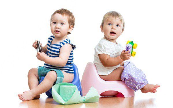 Niños sentados en un orinal