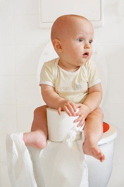 Bebé sentado en el WC
