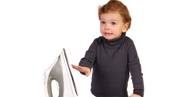 Niño a punto de quemarse con una plancha caliente