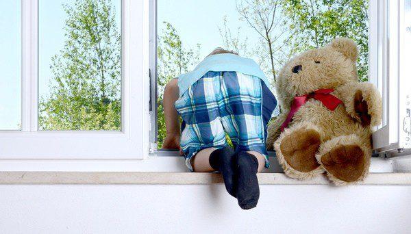 Niño asomándose de forma muy peligrosa por la ventana