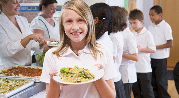 Grupo de escolares en la cola del comedor para recoger su menú diario
