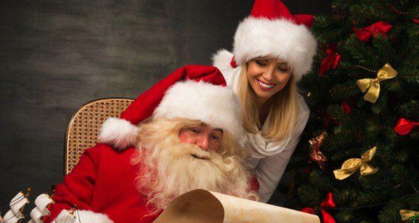 Papá Noel con una ayudante leyendo las cartas enviadas por los niños