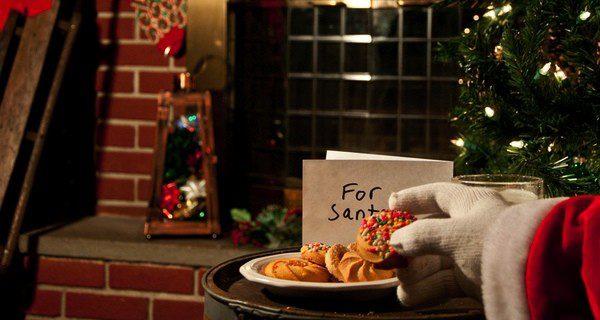 Papá Noel comiéndose las galletas que le han dejado junto al árbol de Navidad y la chimenea