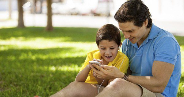 Padre e hijo utilizando juntos el móvil
