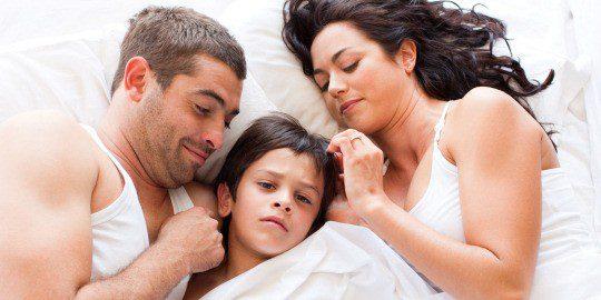Menor con sus padres en la cama