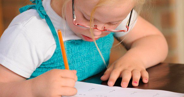 Niña con Síndrome de Down haciendo los deberes