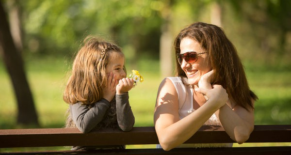 Niña y madre hablando y riéndose
