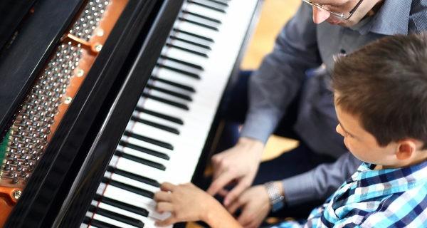 Niño aprendiendo a tocar el piano