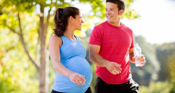 Mujer embarazada y marido caminando