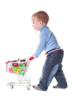 Niño con un carrito de la compra de juguete