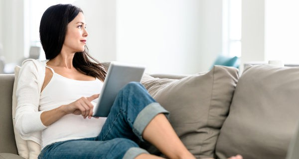 Mujer descansando en el sofá con una tablet