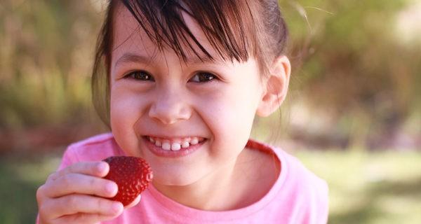 Niña comiendo una fresa