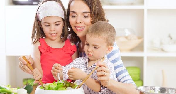 Madre preparando ensalada con sus hijos