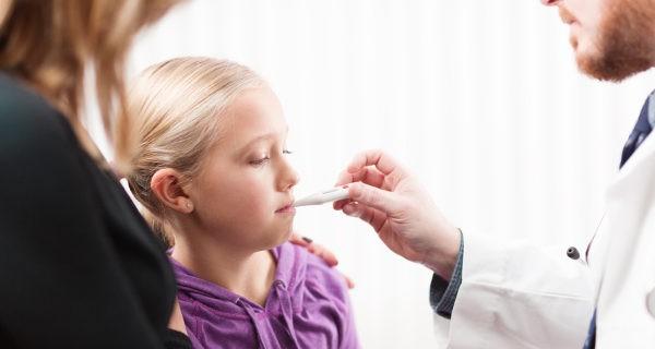Médico tomando la fiebre a una  niña