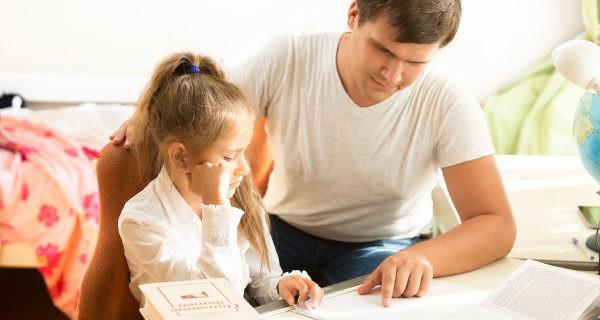 Padre ayudando con los deberes a su hija