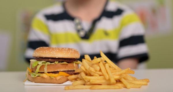 Niño comiendo hamburguesa y patatas