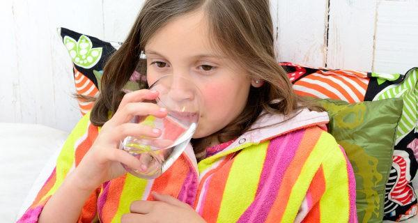 Niña enferma bebiendo agua