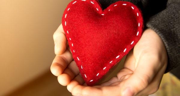 Niño regalando un corazón