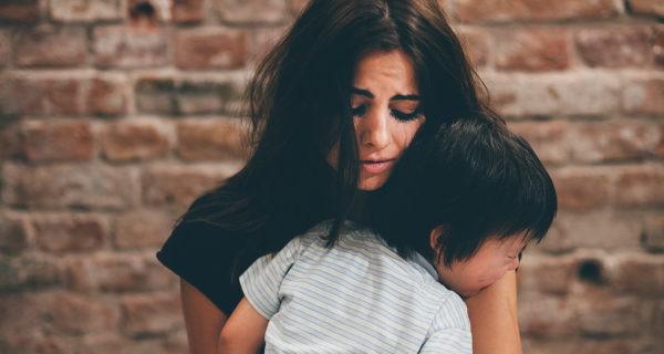 niño llorando abrazado a su madre