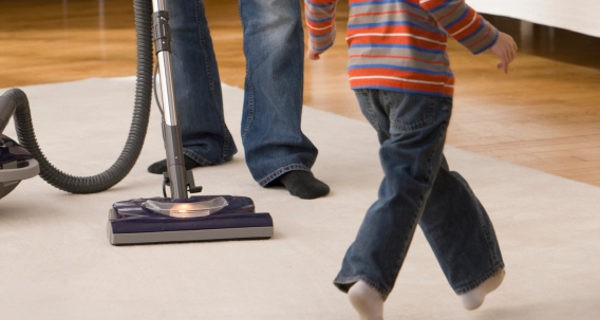 Padre aspirando la alfombra