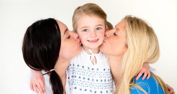 Madres dando un beso a su hija