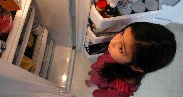 niña buscando comida en la nevera