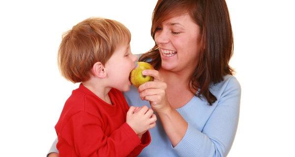 mujer dando fruta su hijo