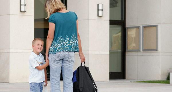 Madre llevando al hijo al colegio