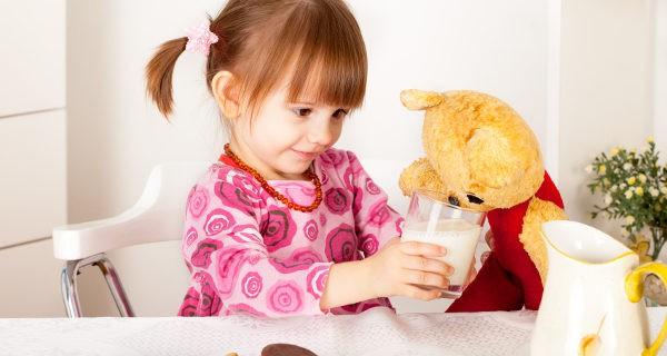 niña compartiendo su leche con un muñeco