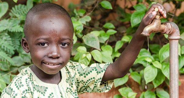 niño africano y grifo de agua