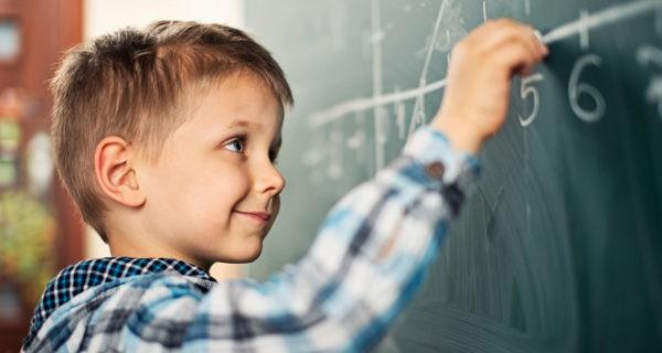 niño en la pizarra de clase