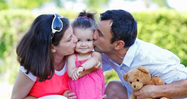 padres dando un beso a su hija