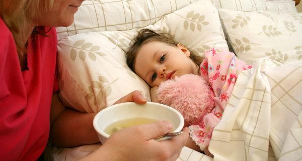 madre dando sopa a niña enferma