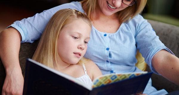 niña leyendo un cuento con su madre