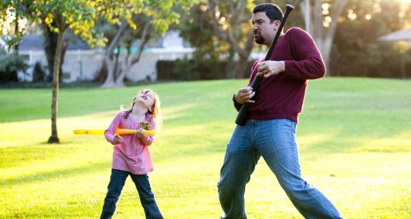 padre e hija bailando en un parque