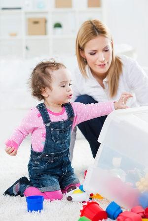 niña recogiendo los juguetes