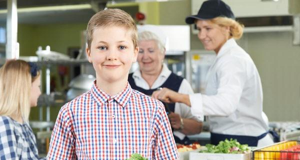 niño en el comedor del colegio