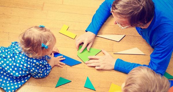 padre jugando a un tangram con sus hijos