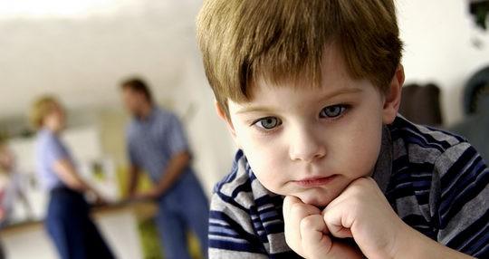 Niño pensativo mientras sus padres mantienen una discusión