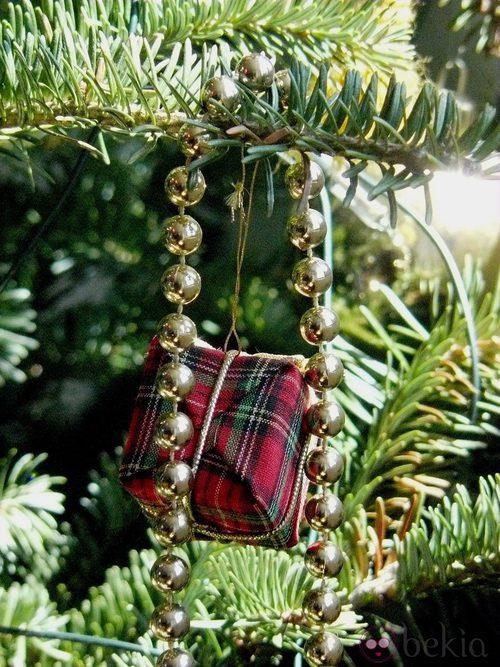 Árbol de Navidad decorado con un collar dorado y regalitos